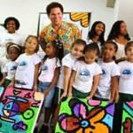 Romero Britto com os quadros por ele desenhados e pintados pelas crianças do Cantinho Feliz