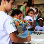 As crianças pintam auxiliadas por Romero Britto