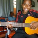 Jovem exibindo o violão novo na aula de música